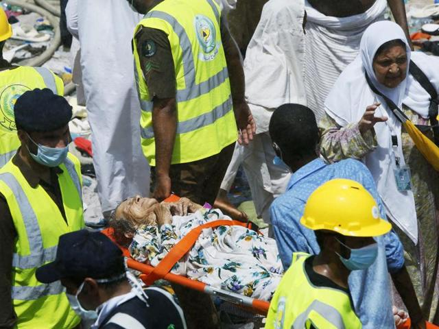 Members of the Saudi emergency services move among the bodies of those killed in a stampede as pilgrims look on, in the Mina neighborhood of Mecca, Saudi Arabia.
