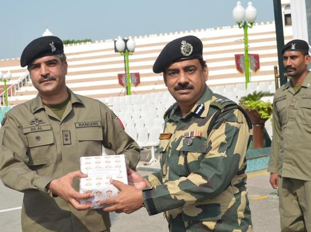 BSF deputy inspector general MF Farooqui (R) exchanging sweets with Pakistan Rangers wing commander Bilal (L) on the occasion of Eid-ul-Adha at Attari Border near Amritsar on Friday.