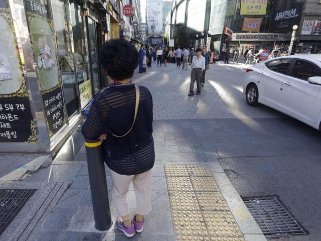 An elderly woman stands at a small, bustling plaza in front of the Piccadilly theatre in Seoul, South Korea. It's a place where elderly prostitutes openly solicit customers for sex in nearby motels.