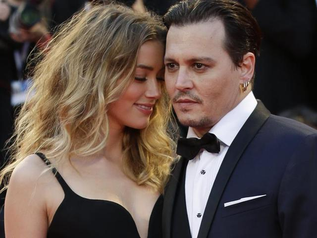 Amber Heard and Johnny Depp pose for photographers at the premiere of Black Mass during Venice Film Festival in Italy.