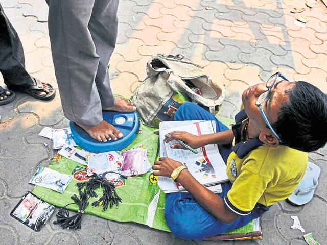 Harendra Singh, 13, completes his homework while waiting for passersby to step on his weighing scale outside the Noida City Centre Metro station.