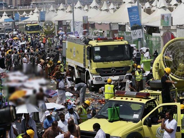 Members of the Saudi emergency services move among the bodies of those killed in a stampede as pilgrims look on, in the Mina neighbourhood of Mecca, Saudi Arabia.