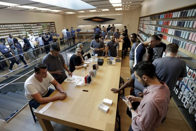 People check out new iPhone 6s Plus mobile phones as the Apple iPhone 6s and 6s Plus go on sale at an Apple Store in Los Angeles, California