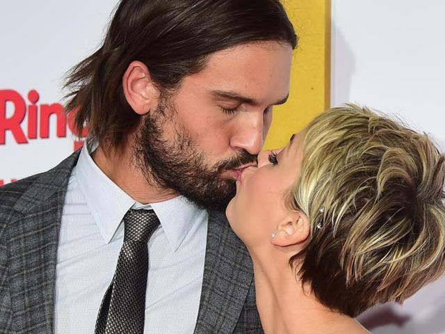 This January 6, 2015 file photo shows Kaley Cuoco-Sweeting and husband Ryan Sweeting kissing on arrival for the world premiere of the film The Wedding Ringer in Hollywood, California.