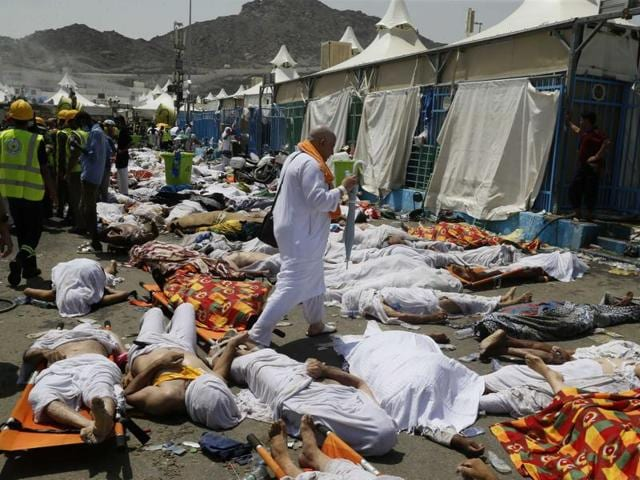 A muslim pilgrim walks through the site where dead bodies are gathered in Mina, Saudi Arabia during the annual haj pilgrimage on Thursday, Sept. 24, 2015.