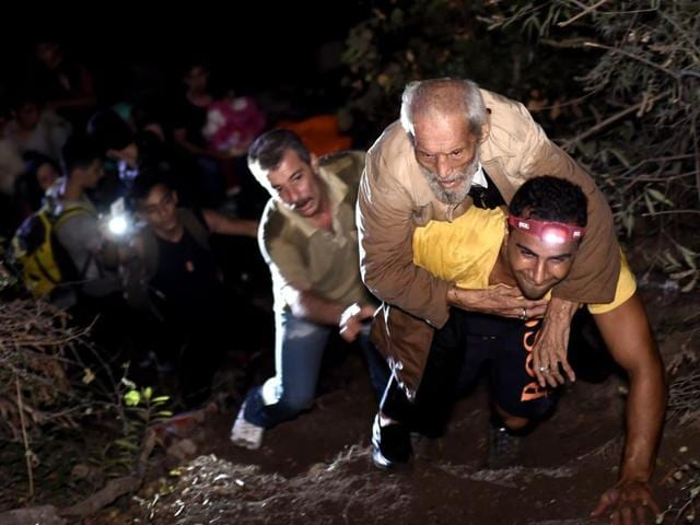 A man helps an elderly man to climb a slope after they arrived, with other refugees and migrants, to the Greek island of Lesbos after crossing the Aegean sea from Turkey.