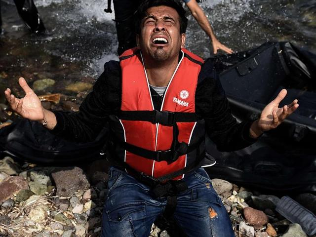 A man reacts as he arrives with other refugees and migrants to the Greek island of Lesbos after crossing the Aegean sea from Turkey.