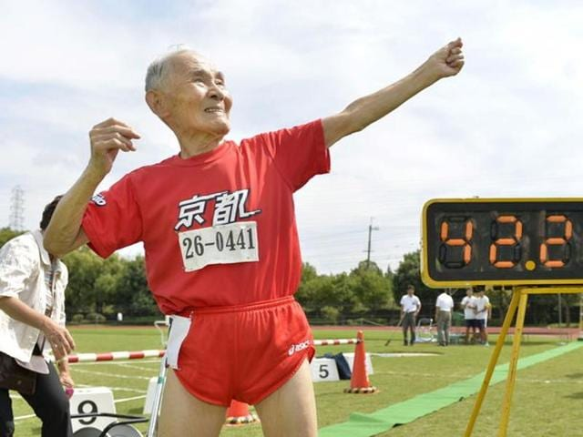 105-year-old Japanese Hidekichi Miyazaki poses like Jamaica's Usain Bolt in front of an electric board showing his 100-metre record time of 42.22 seconds at an athletic field in Kyoto, Japan.