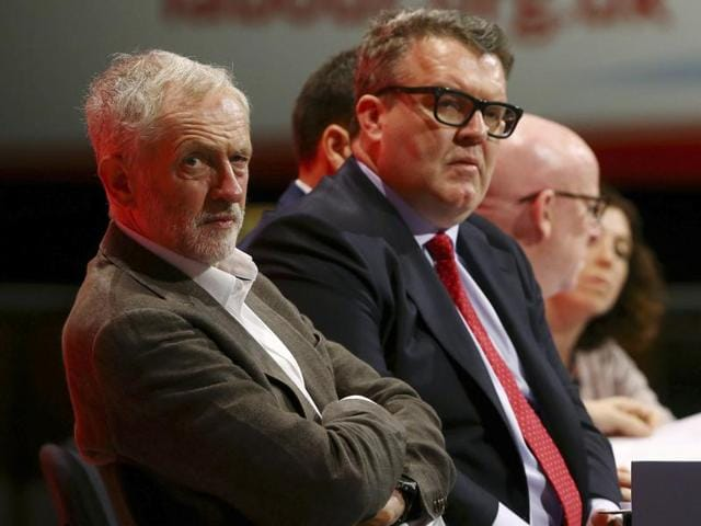 Britain's Labour party leader Jeremy Corbyn, left, with deputy leader Tom Watson, centre, listen to speeches during the Labour Party annual conference at the Brighton Centre in Brighton, England, Sunday Sept. 27, 2015.