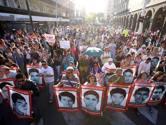 Thousands of people march asking justice as they hold banners of 43 missing Mexican students of the Ayotzinapa Rural Teachers' College during a rally marking one year anniversary since their disappearance, in Guadalajara, Mexico, 26 September 2015.