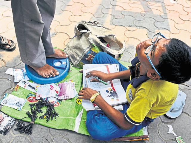 13-year-old, Harendra, sits outside Noida City Centre metro station with weighing scales and completes his homework while waiting for customers in Noida.