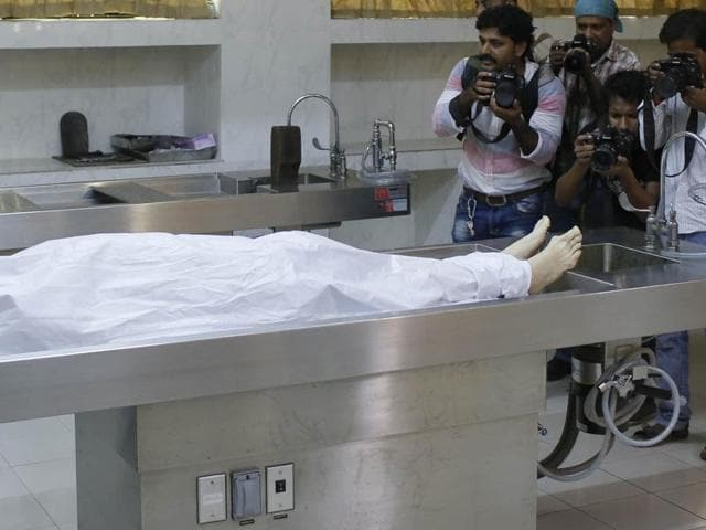 Journalists take photographs as the body of Italian citizen Cesare Tavella who was gunned down by assailants is kept at a hospital morgue in Dhaka, Bangladesh.