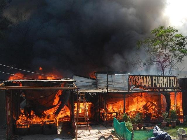 Fire fighters trying to douse the fire which broke out in the furniture market Sec-53 in Chandigarh on Monday