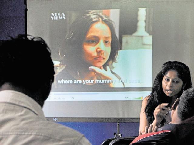 A representative from the drive shows a film to highlight the plight of missing children in Jaipur on Monday.