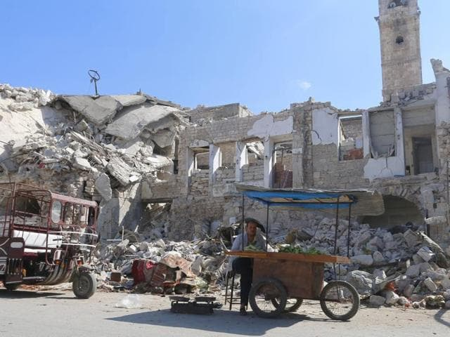 A vendor sit by his cart near damaged buildings inside a market in the northwestern city of Ariha, in Idlib province, Syria.