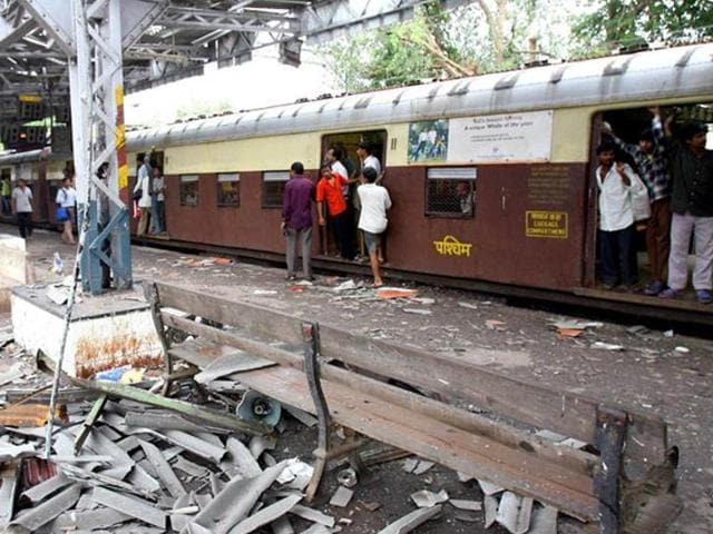 In this file photograph taken on July 12, 2006, commuters walk past the blast site at Mahim railway station in Mumbai, the day after a wave of coordinated blasts on commuter trains in Mumbai.