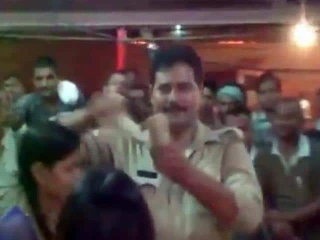 A screengrab of the video in which a policeman is seen throwing notes at dancers during a religious ceremony in Varanasi.