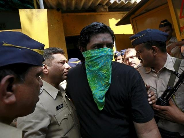 One of the 12 men, convicted of planning several blasts on crowded commuter trains in Mumbai in 2006, is escorted by police to a court in Mumbai, India, September 30.