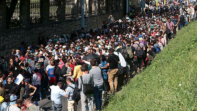Hundreds of migrants walk after leaving the transit zone of the Budapest train station, walking towards the Austrian border.  Austria's interior minister says the country is considering closing the border in the face of the increasing number of migrants fleeing towards Germany.