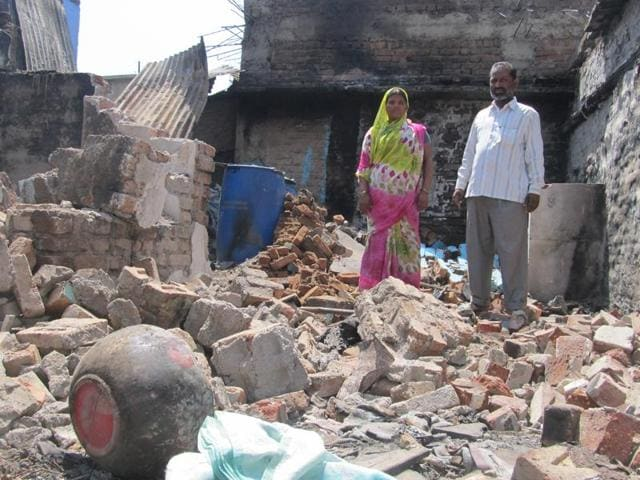 Parveen Momin and Mehboob Momin stand amid the ruins of their house that was attacked with petrol bombs by alleged activists of the Sri Rama Sene in Mudhol, Bagalkot.(HT Photo)