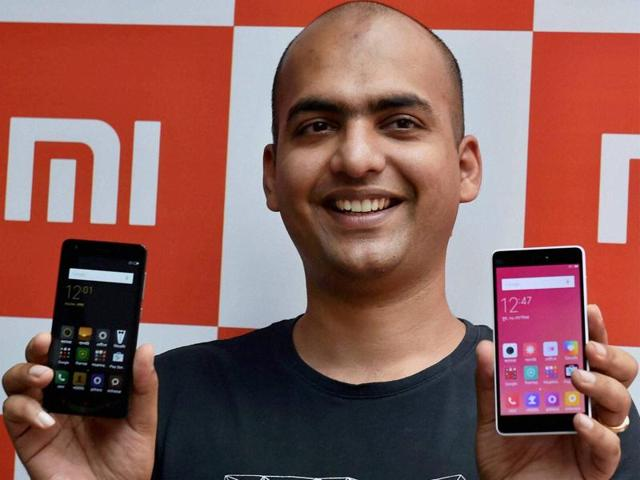 Xiaomi's India head Manu Jain displays the new phones during a launching event in Kolkata.