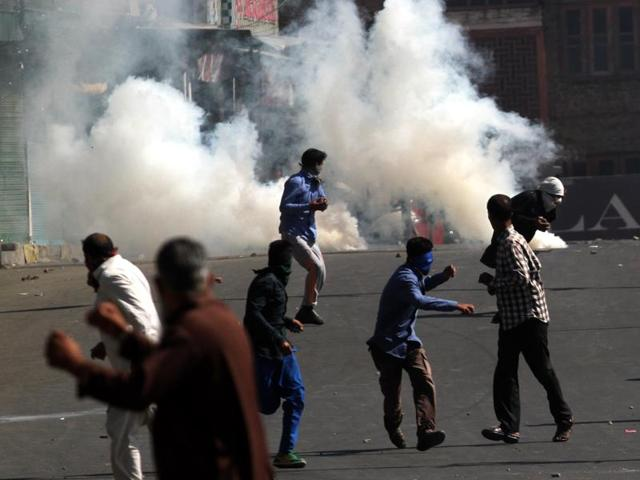 Kashmiri protesters run for cover as police fire tear gas shell to disperse them during a protest against the decision of the Jammu-Kashmir high court about implementing the ban on the sale of beef the state.