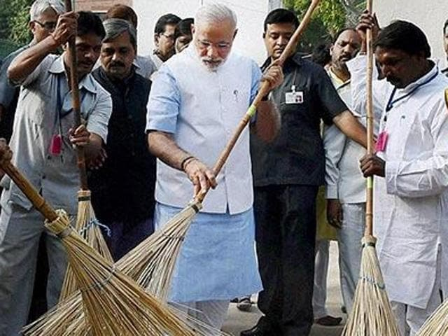 A file photo of Prime Minister Narendra Modi wielding a broom with NDMC workers to launch the 'Swachh Bharat Abhiyan' in Valmiki Basti in New Delhi.(PTI File Photo)