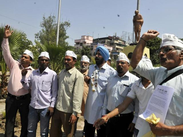 Aam Aadmi Party activists stage a demonstration at Regal Square in protest against the attack on journalists by petrol pump employees, in Indore on Wednesday.