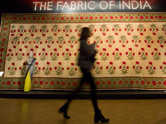 A visitor walks past a floor-spread during a press preview of