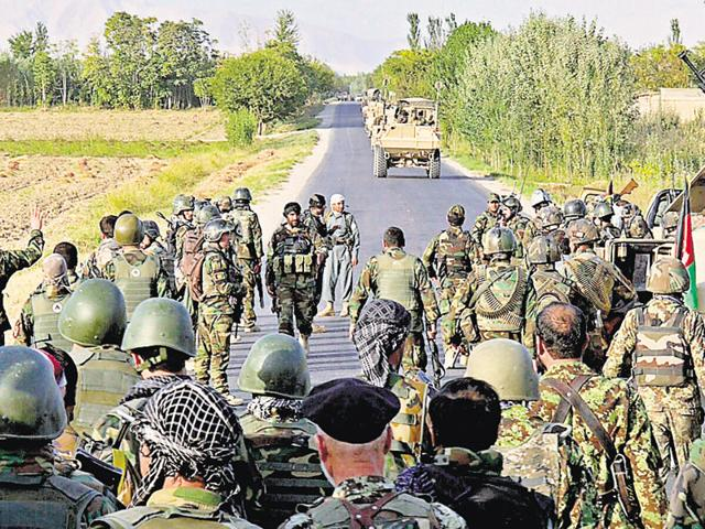 Members of the Afghan security services and National Army (ANA) secure a road leading to the Baghlan-Kunduz provincial border, Afghanistan, on Wednesday.
