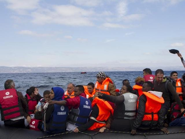 Refugees and migrants arrive on an overcrowded dinghy on the Greek island of Lesbos, after crossing a part of the Aegean Sea from the Turkish coast October 1, 2015.