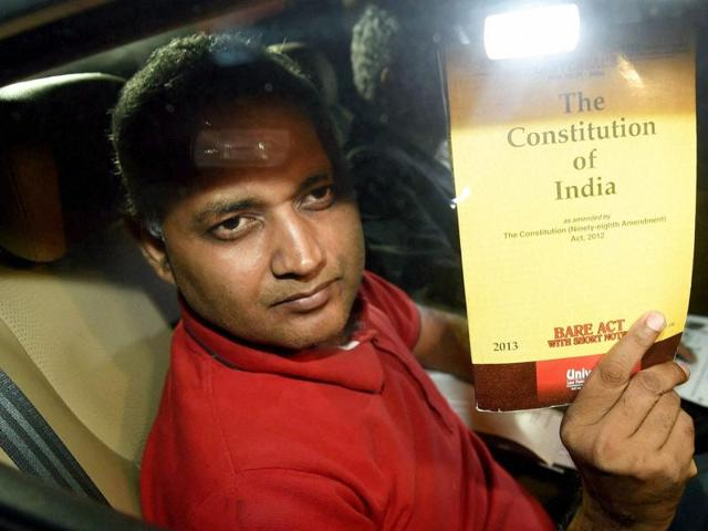 New Delhi: AAP MLA Somnath Bharti shows a book of Constitution of India as he arrives to surrender at the Dwarka North Police Station in New Delhi on Monday. PTI Photo by Manvender Vashist (PTI9_28_2015_000359a)