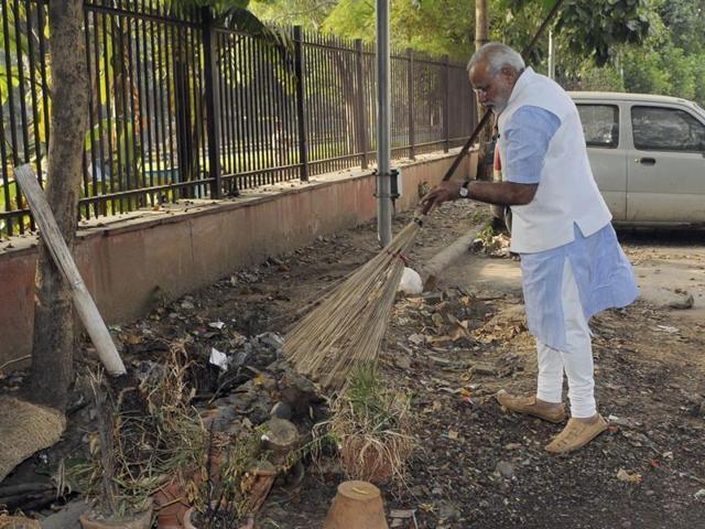 Narendra Modi wields a broom with NDMC workers to launch 'Swachh Bharat Abhiyan' in Valmiki Basti in New Delhi.(PTI Photo)