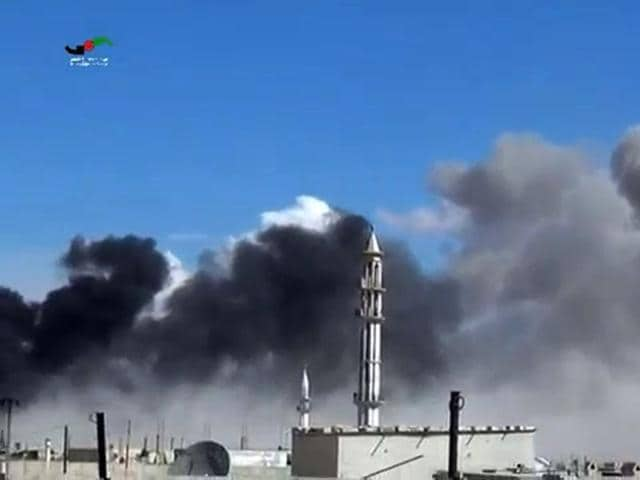 An image grab taken from a video released by the Homs Media Center on September 30, 2015 shows smoke billowing from buildings and a minaret in the central Syrian town of Talbisseh in Homs province.