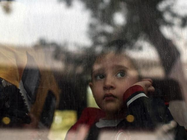 A refugee child looks through a bus window as they leave for Istanbul, abandoning plans to cross to Europe near Turkey's western border with Greece and Bulgaria, in Edirne.