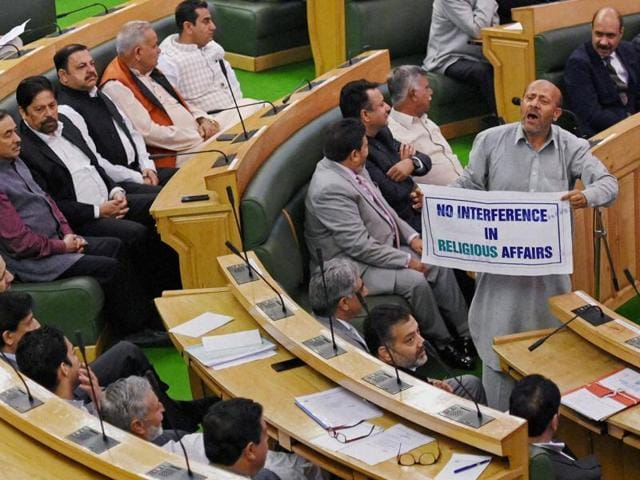 MLA Sheikh Abdul Rashid holds a banner as protest against  the Beef ban by J&K high court on the first day of autumn session of the state assembly in Srinagar on Saturday.