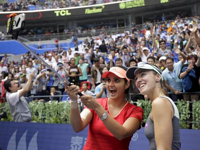 Martina Hingis of Switzerland (R) and Sania Mirza of India pose for pictures as they celebrate after winning their women's doubles final match against Irina-Camelia Begu and Monica Niculescu of Romania, at the Wuhan Open tennis tournament.