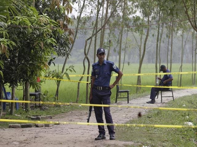 Bangladeshi security officers stand by the site where a Japanese Kunio Hoshi was killed at Mahiganj village in Rangpur district, Bangladesh, Sunday, Oct. 4, 2015.