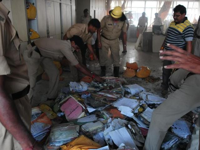 Firemen try to save some files after fire broke out on the 5th floor of the Vindhyachal Bhawan in Bhopal on Sunday.