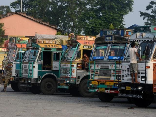 Indian truck drivers wait outside a customs office for clearance onward into to Nepal at Kakarbhitta on the eastern Nepalese border with India on October 4, 2015.