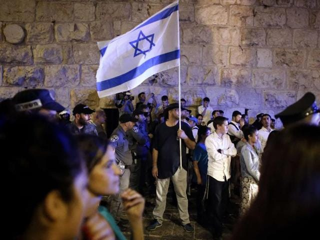 Israeli extreme far-right supporters demonstrate against Palestinians at one of the gates of the Jerusalem's Old City. Tensions soared after a Palestinian, with a gun and a knife, killed two people and wounded a child.