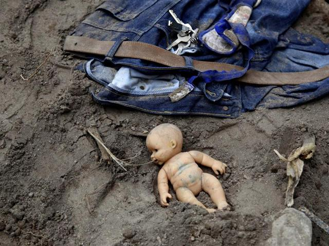 In this Saturday, Oct. 3, 2015 photo, a doll and clothing lay in the mud as rescue workers continue to search the site of a mudslide in Cambray, a neighborhood in the suburb of Santa Catarina Pinula, on the outskirts of Guatemala City.