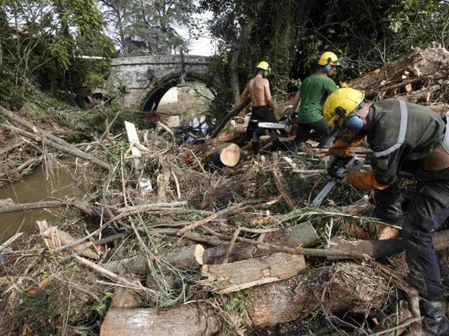 Men saw trees near a stream as they clear away debris the day after torrential rains caused flooding in Biot, France, October 5, 2015.