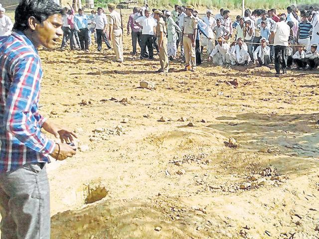 Police officials and locals near the borewell in which the toddler fell in Dausa district on Sunday.