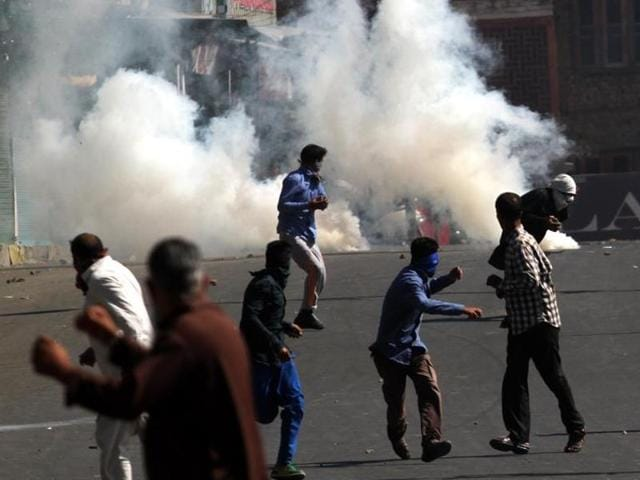 File photo  of  Kashmiri protesters running for cover as police fire tear gas shell to disperse them during a protest outside the Jamia Masjid in Srinagar, Kashmir, India.They were protesting  the decision of the Jammu Kashmir High Court about implementing the ban on the sale of beef in Jammu and Kashmir.