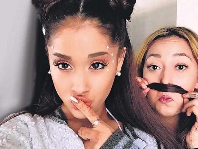 Singer Ariana Grande sporting twin braided knots while Vanessa Hudgens does Princess Leia double buns.