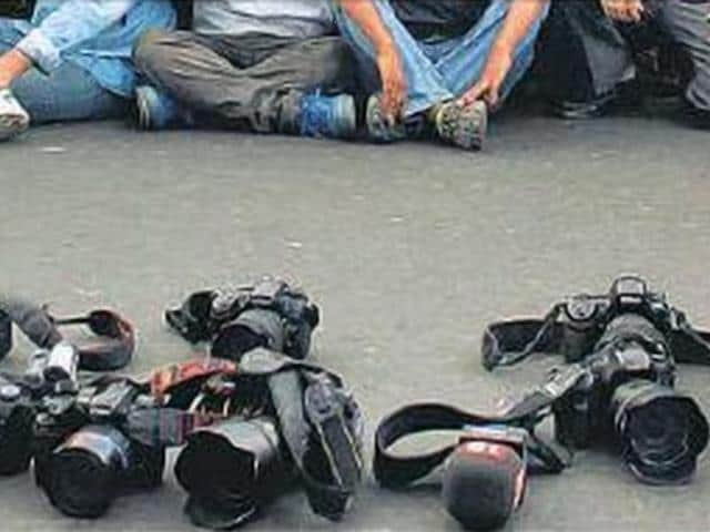 Photographers lay down their cameras during a rally by journalists on Monday to protest against the assault on them by goons during the civic polls.
