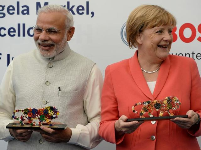 Prime Minister Narendra Modi  and German Chancellor Angela Merkel smile after receiving the logo of Modi's pet project