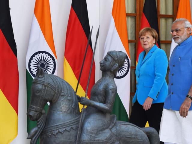 PM Narendra Modi (R) walks with German Chancellor Angela Merkel as they arrive for meetings at Hyderabad House in New Delhi on Monday.