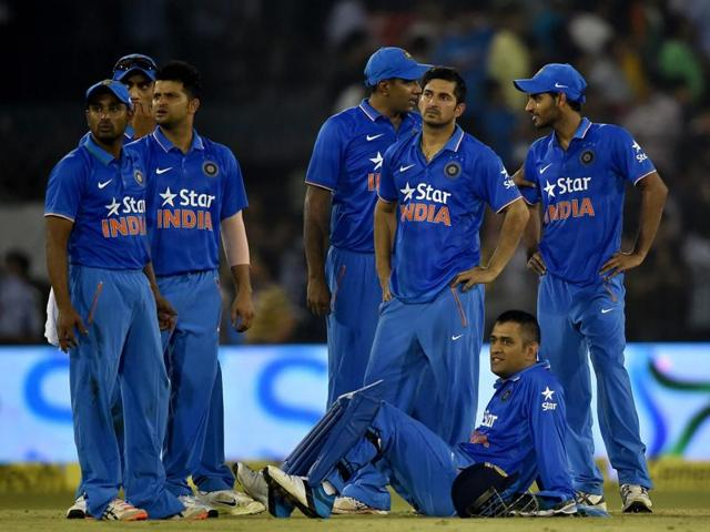 M S Dhoni and his teammates wait out as play is interrupted by spectators during the second T20 cricket match against South Africa in Cuttack on Monday.